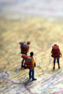 miniature figurines of backpack travelers on a map